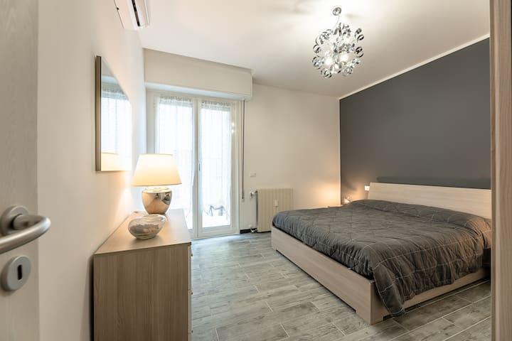camera matrimoniale con grande armadio ad ante scorrevoli, cassettiera e due comodini, accesso alla terrazza dalla porta finestra