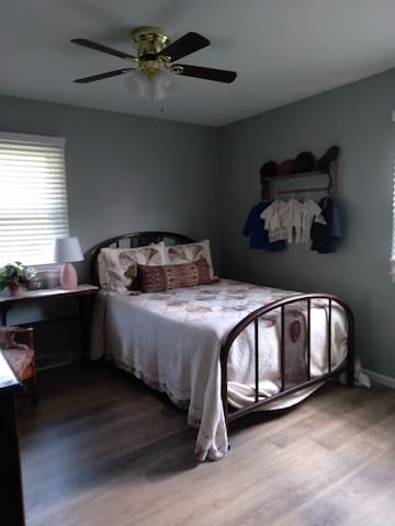Full sized bed in bedroom at end of hall.