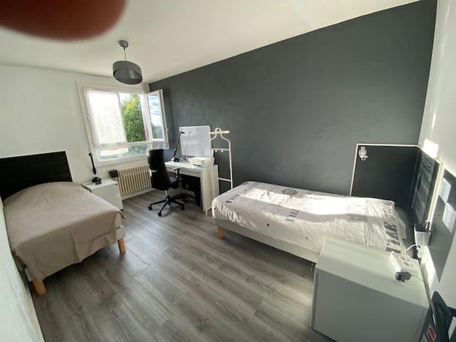 chambre avec 2 lits simples équipée d'un bureau avec imprimante
