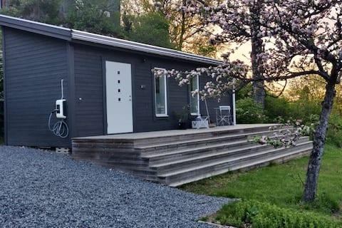 Mysigt minihus med altan, gräsmatta och parkering.