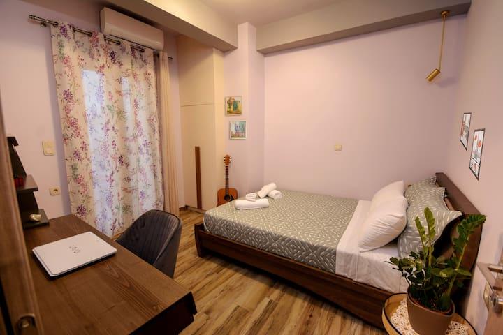 Υπνοδωμάτιο με ευρύχωρο διπλό κρεβάτι από ξύλο ελιάς και ασορτί σύνθεση γραφείου, κατάλληλο για εργασία ή ψυχαγωγία.