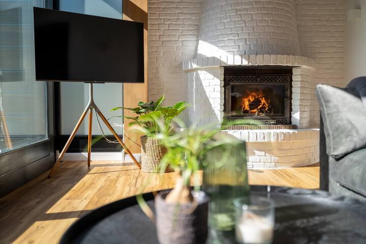 das wohnzimmer lädt zum entspannen ein. auch hier finden sich smart-tv für netflix & co - sowie ein kamin für warme, kuschelige und hyggelige abende.