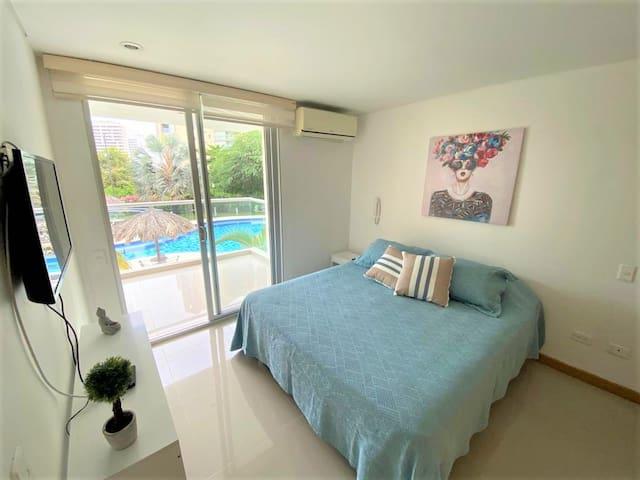 Habitación con cama Queen, baño privado, aire acondicionado, TV, acceso al balcón.
