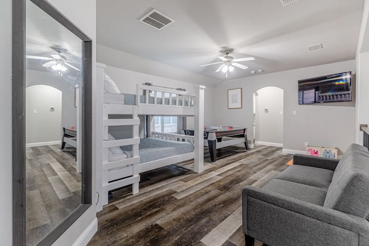 Upstairs game room with a 55in tv, air hockey/pool table, queen size bunk bed and a couch that converts into a twin size bed.