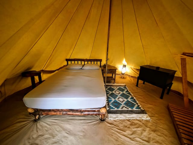 We have created a cozy environment inside the teepee.  There is a Queen size bed, nightstands, a coffin with a lock to keep personal items, a fan, and a cloth rack.