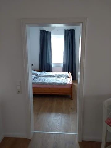 Kleines Schlafzimmer mit massivem Holz-Doppelbett ( 1,80 breit) mit Nachtschränken,  Regal (kein Kleiderschrank) und blickdichten Vorhängen