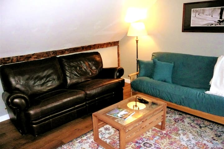 Time to relax - Airy living room with a couch recliner, futon sleeper, recliner chair and TV.