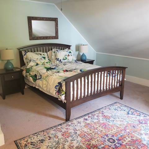 Queen size bedroom with recliner by the window and large HD TV