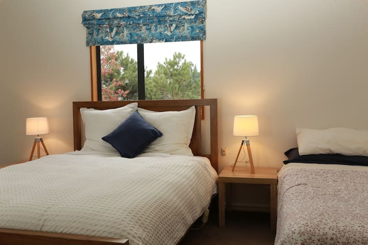 Large sunny room. Queen bed and single bed with garden views.