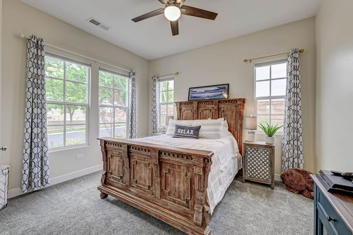 Guest bedroom with a queen size bed, large closet, Smart TV, and operating windows.