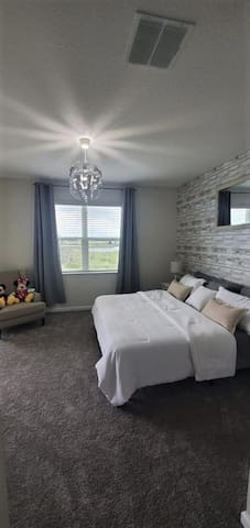 Master Bedroom, equipped with King-sized bed and smart t.v. the master bedroom has access to a satisfying view of one of the champions gate many beautiful lakes, a private entrance to the master bathroom, and just a sliding door away from the balcony