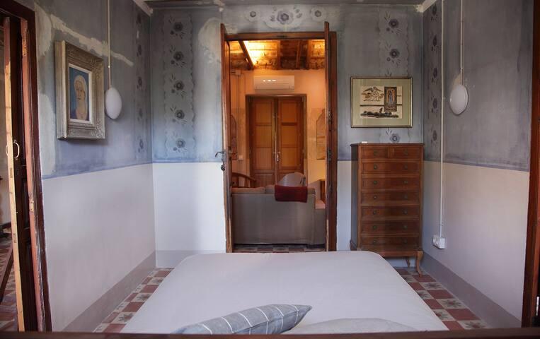 Habitación principal con cama de matrimonio, puerta de la terraza al fondo