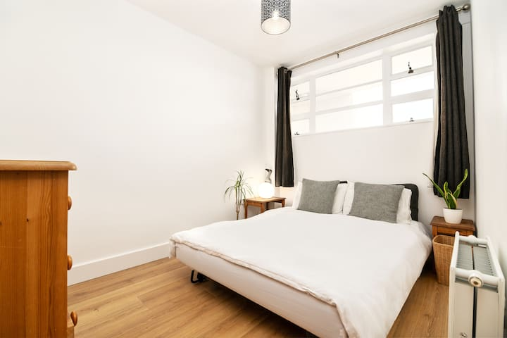 Spacious double bedroom with wooden chest of draws, clothes rail with hangers, towel rack, bedside tables and lovely natural light.