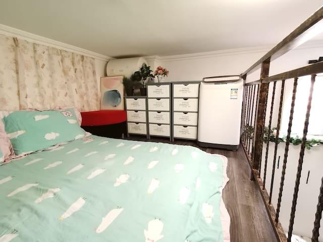 床以及床旁边的柜子和洗衣机。