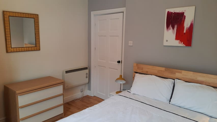 Bedroom with king size bed, hypoallergenic 13.5 tog downie, chest of drawers and wardrobe for storage.