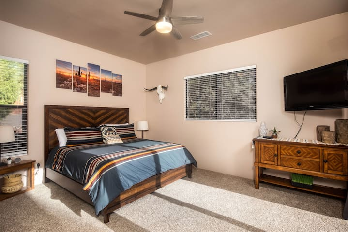 Second suite features a king bed, closet space, TV with Roku, sliding door to front porch, and attached bathroom.