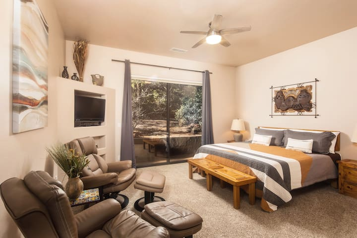 Main bedroom features a king bed, sliding door to backyard, sitting area, TV with Roku, walk-in closet and attached bathroom.