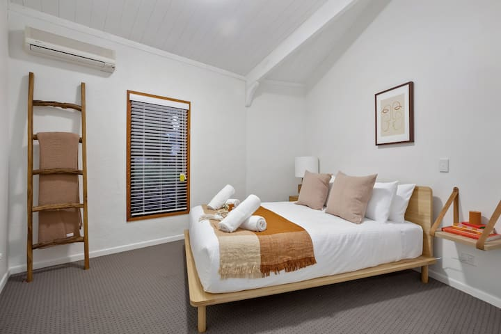 The bright and modern third bedroom has a queen-sized bed dressed in plush hotel-quality linens ready for you to sink into.