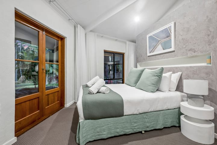 The beautiful second bedroom opens to the garden and is fitted with a premium queen-sized bed. It has a large wardrobe for storing your belongings.