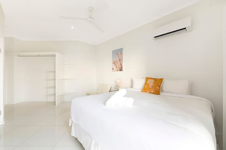 The master bedroom has a king bed, large sliding glass doors showcasing water views and access to the balcony, and a modern ensuite.