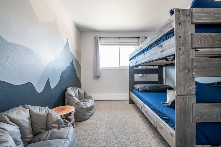 """""""The Kid's Bunk Room"""" features a custom mural of mountains, paired with two comfy bean bag chairs and every kid's dream while on vacation - BUNK BEDS!"""