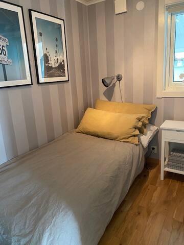 Mindre sovrum nere med enkelsäng samt nattduksbord och garderob.