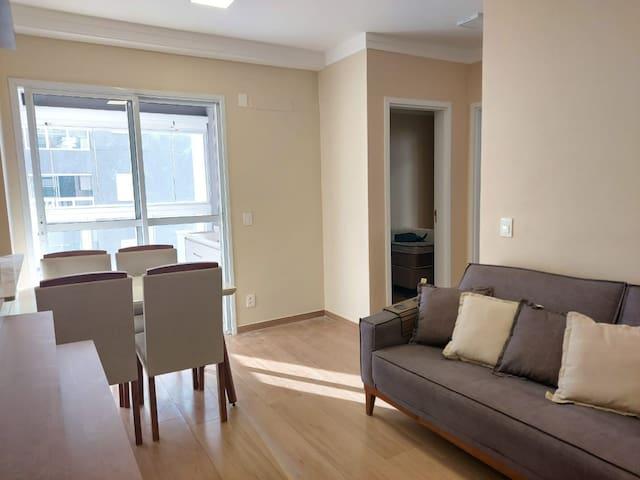Sala para dois ambientes, TV e sala de jantar, muito iluminada