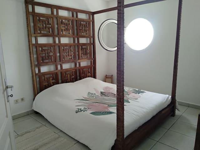 Chambre confortable disposant d'un lit à baldaquin queen size (160x200) et de la climatisation.