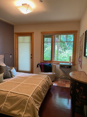 guest room with queen size Casper bed outside access window coverings