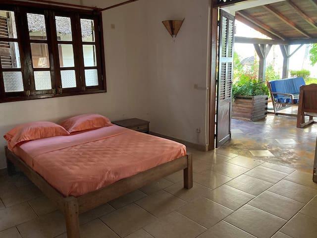 Chambre 1: Chambre au rez-de-chaussée. Elle a une grande fenêtre, une grande porte qui donne sur la terrasse.