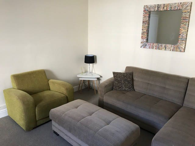 Lounge with sofa bed, dining table and smart TV.