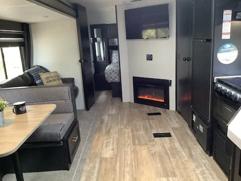Cozy RV in country setting with a yard full of fun