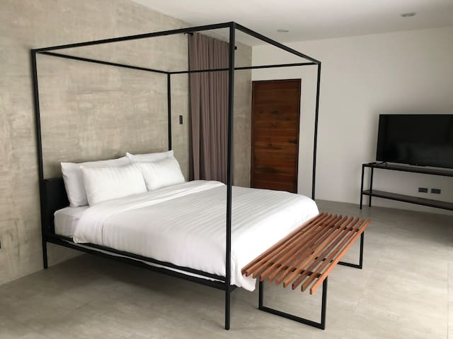 Similar to the first bedroom, the second bedroom features a king-size bed, work desk, Smart TV, and private bathroom with basic toiletries.