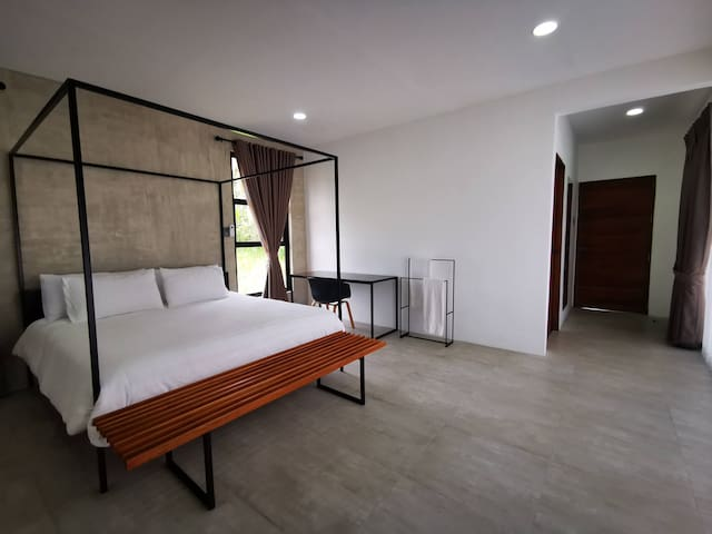 The first bedroom features a king-size bed, work desk, and private bathroom with basic toiletries.
