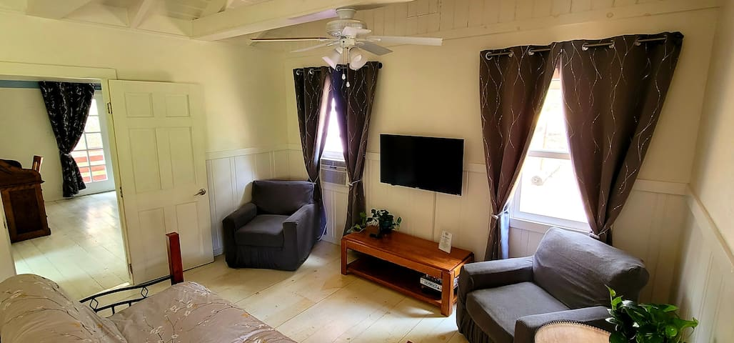 living room with futon, window air conditioner and TV