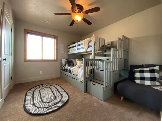 Bunk room with two full beds, a twin bed, and a twin pull out sleeper chair.