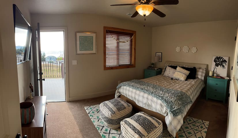 Upstairs bedroom with queen bed, charging docks, and private deck with the best lake view in the house. Sunrise viewing recommended.