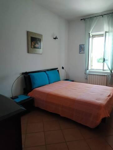 Camera da letto con letto matrimoniale, ampio armadio a muro, cassettiera e bagno in camera completo di doccia.