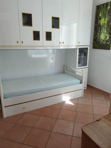 Camera da letto con letto singolo e altro letto singolo estraibile, scrivania, armadio e cassettiera.
