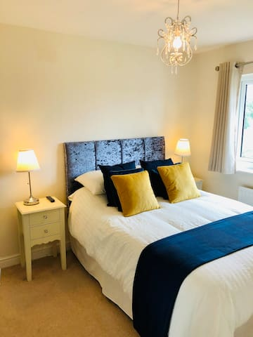 Double bed in Bedroom 1 with a Kingsize duvet and there is a large wardrobe.