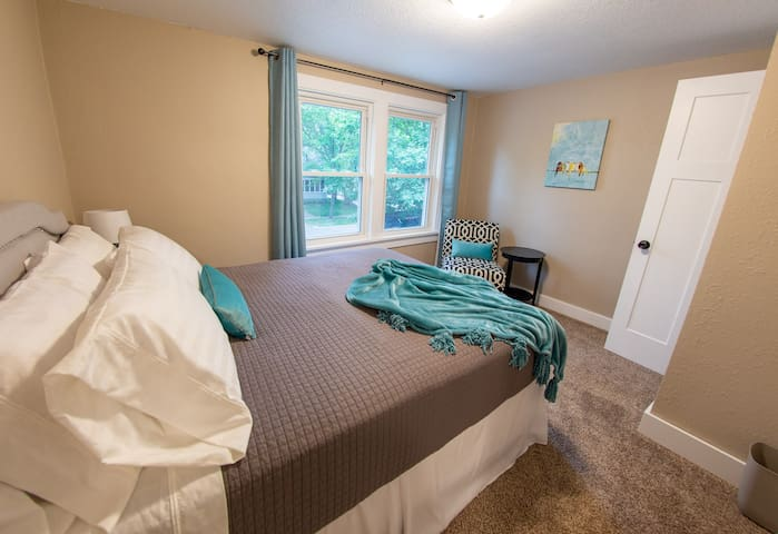 Bedroom #1 features a queen bed luxury linens and an array of pillow options and a chair to relax in at the end of the day