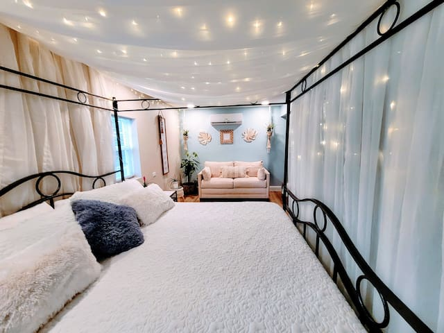 This King Size Temper-pedic wonder bed provides the restful slumber your body is craving. It's surrounded in a wrought iron canopy, draped in fairy twinkle lights and elegant fabric. Delight your senses as you drift off to a magical dreamland.