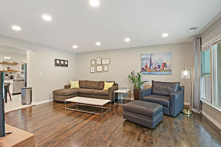 Spacious living room with hardwood flooring, a comfortable couch from Crate & Barrell with a chaise lounge, and an oversized leather chair from Room & Board. Relax!