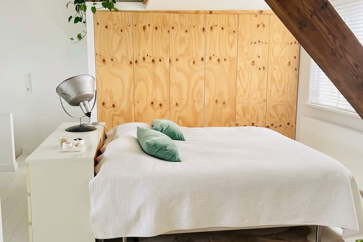 Slaapkamer zolder, met 2-persoons bed en eigen badkamer met bad, inloopdouche, 2 wastafels en apart toilet