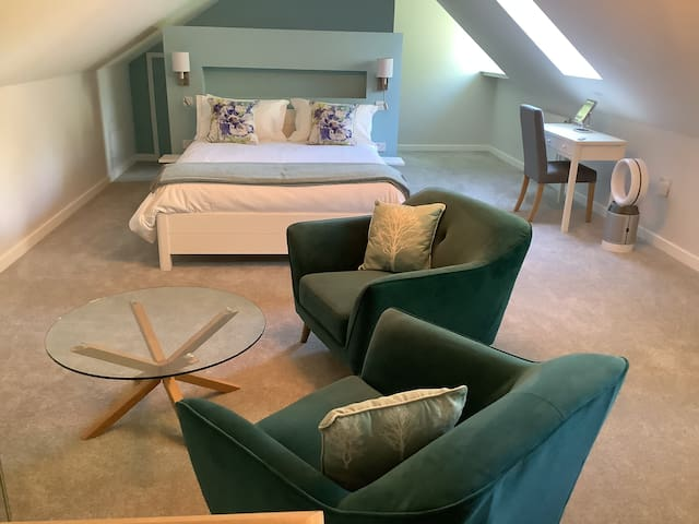 A large attic bedroom (with some head restrictions at sides only).King size bed with hypnos mattress Beautiful ensuite with large shower,bath,toiletries and thick cotton towels. Desk and Dyson fan. Full breakfast each morning, come and enjoy soon!