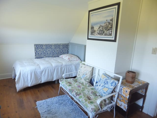 One of the upstairs bedrooms, plenty of natural light and beautiful sunsets can be seen from the window in this room. It also contains two small closets.