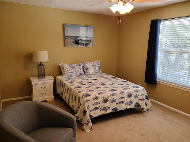 """Primary bedroom with a 32"""" Smart TV"""