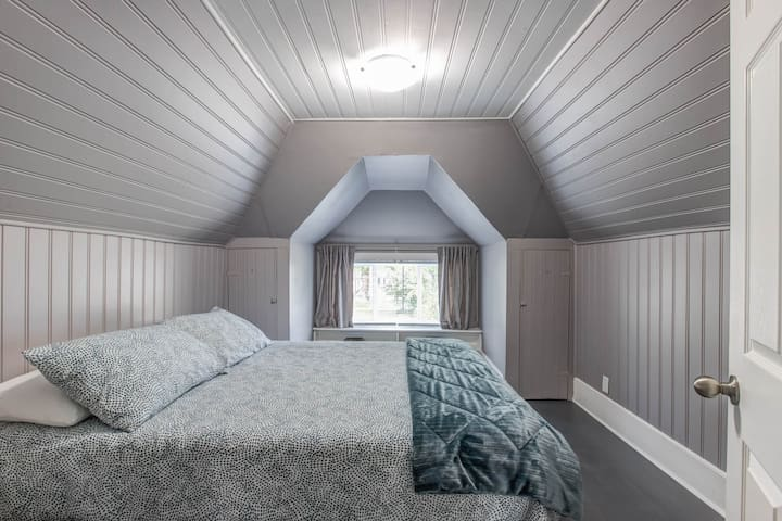 Loft bedroom facing front street with brand new queen size Endy mattress, cotton sheets, and duvet.    Fall asleep with the windows open for fresh air and listen to the leaves rustling in the three giant elm trees that line the property.