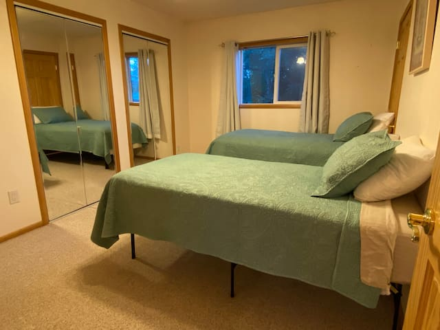The bedroom currently has two twin beds with lamps for each a small fan, and a power strip for your phones. The double mirrored doors are closets. The back window looks out onto trees and the main house.