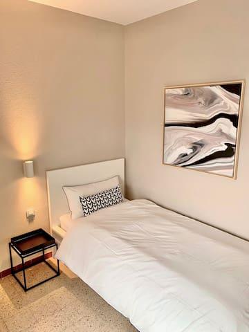 """Der """"Sunset Room"""" (Einzelzimmer mit einem Bett 0,90x2,00m) bietet Platz für eine Person und ist in warmen, hellen Farben eingerichtet."""